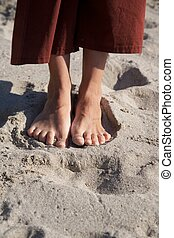 woman feet on beach sand