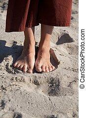 woman feet on beach sand