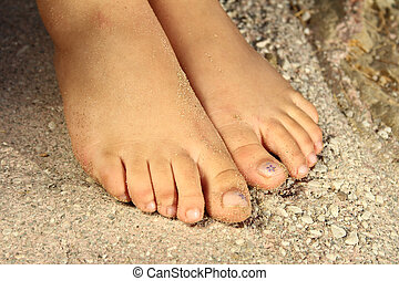 Woman feet on sand