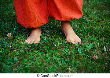 woman feet on the grass with orange pants