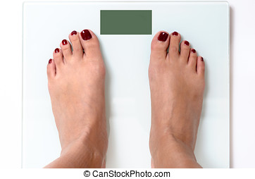 Woman feet on weight scales - Close-up of woman feet with...