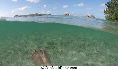 Woman feet snorkeling split view - Split view of female feet...
