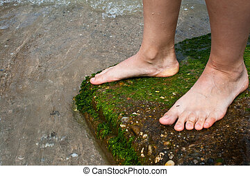 Woman feet standing on a rock near the water