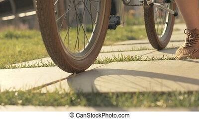 Woman feet walking next to riding bike on paved path slow...