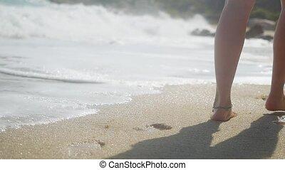 Woman feet wearing bracelet walking on tropical beach leaving footprints in sand in slow motion. 1920x1080