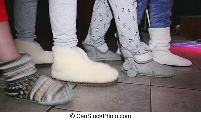 Woman feets in soft slippers synchronously tap on floor. Party in nightclub.