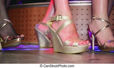 Woman feets on high heels synchronously tap on floor. Runway show in nightclub.