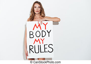 Woman feminist holding nameplete with slogan ''My body my...