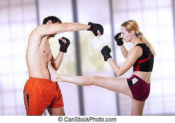 young pretty sexual girl is protected from attack of man - front leg kiking in stomach. Martial art - kickboxing; cardio boxing; muay thai; taekwondo; Jiu-jitsu; kungfu or mma