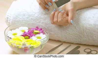Woman filing nails in spa salon.