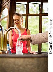 woman fillig a plastic bottle