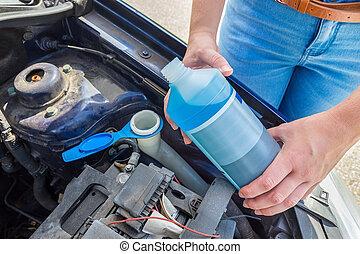 Woman filling car reservoir with blue fluid in bottle -...