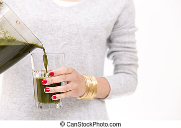 Woman filling glass with smoothie for breakfast