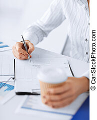 woman filling in blank paper and drinking coffee