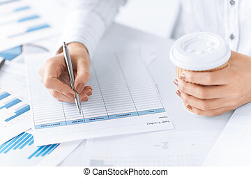 woman filling in form and drinking coffee