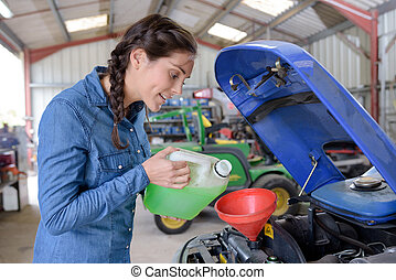 woman filling petrol in tractor