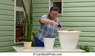 Woman Filling Pot With Soil