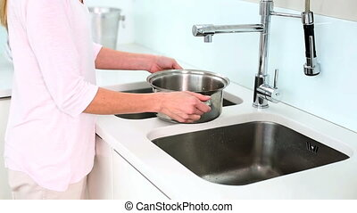Woman filling water on saucepan in kitchen at home