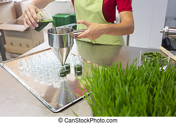 Woman filling wheatgrass smoothie in glasses