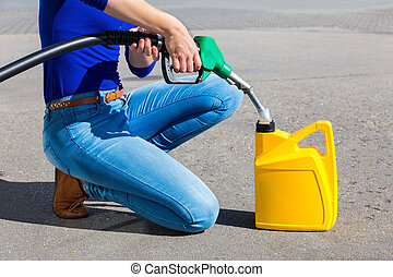 Woman filling yellow can with gasoline or petrol