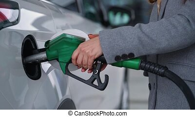 Woman fills petrol into her car at a gas station closeup -...