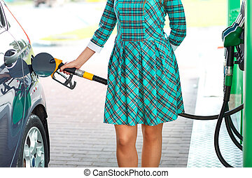 Woman fills petrol into the car at a gas station