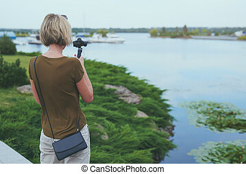 Woman filming with small personal camera