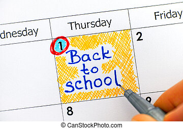 Woman fingers with pen writing reminder Back to School in calendar. September the 1st.