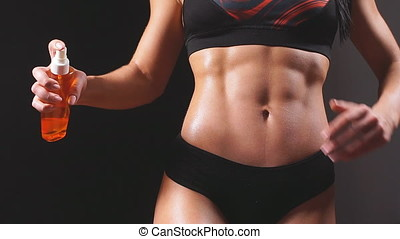 Woman fit fitness female model applying moisturizing body...