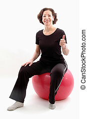 woman fitness ball - smiling woman on fitness ball thumbs up...
