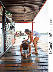 woman fitness instructor assisting young woman in exercise...