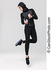 Woman fitness muslim posing isolated over white wall background make exercises with dumbbells.