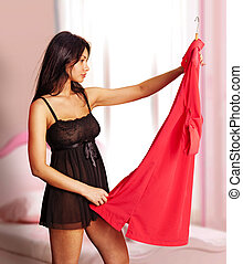 woman fits on red dress in bedroom