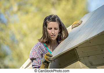 Woman fitting a roof to a wooden garden hut