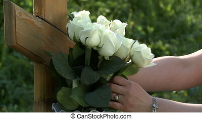 Woman fixes white roses on wooden tombstone - View of woman...