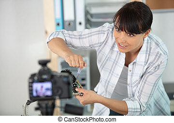 woman fixing a pc component in front of a camera