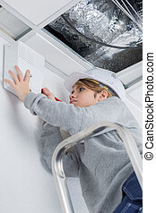 woman fixing ceiling at home