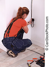 Woman fixing electrical socket