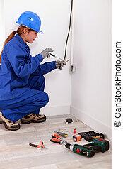 Woman fixing house electrics