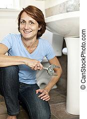 Woman fixing plumbing