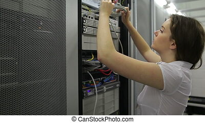 Woman fixing wires and smiling - Female technician fixing...