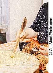Woman flattening bread
