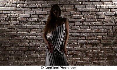 Woman flexible in high heels dance against a brick wall