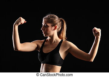Woman flexing muscles in workout - Sexy young woman wearing...