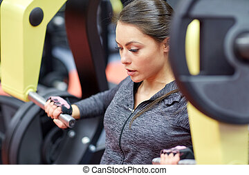 woman flexing muscles on chest press gym machine - fitness, ...