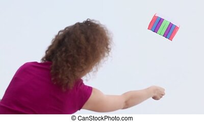 Woman flies kite and holds rope, view from behind at day