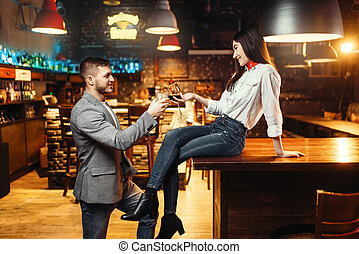Woman flirting with man, couple at bar counter