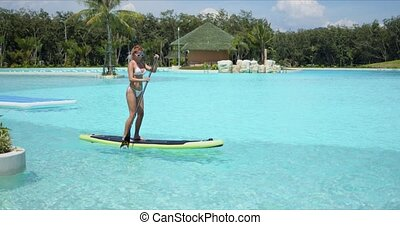 Woman floating on paddle board in large swimming pool - Side...