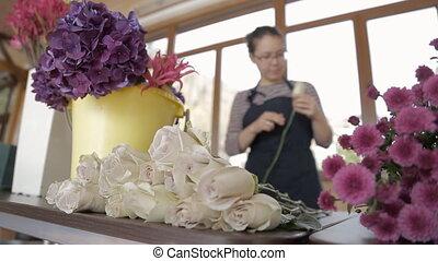 Woman florist breaks off leaves on stems of long white roses among flowers.