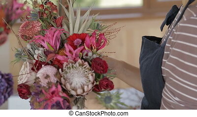 Woman florist creates bouquet of flowers indoors. Female...
